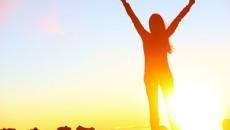 Happy celebrating winning success woman at sunset or sunrise sta