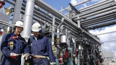 oil-engineer-workers-in-front-of-large-pipeline-and-fuel-construction-inside-refinery